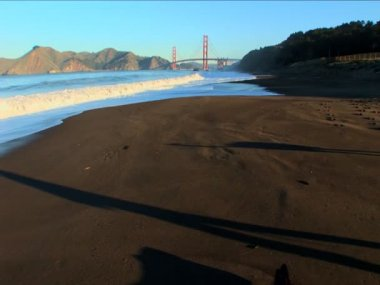 Distant view of San Francisco's Golden Gate Bridge & ocean waves — Stock Video