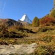 Fall in alpine meadow Zermatt with hikers & Matterhorn — Stock Video #19490363
