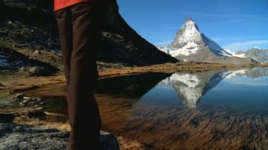 Female hiker in beautiful alpine landscape with lake & Matterhorn peak — Stock Video
