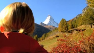 Fall in an alpine meadow Zermatt with female hiker & the Matterhorn — Stock Video