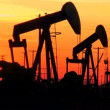 Oil donkeys or pump jacks in perpetual motion at sunset - Stockfoto