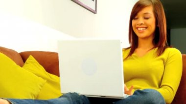 Young girl relaxing at home while using a laptop computer — Stock Video