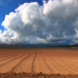 Dramatic time-lapse clouds over a ploughed field - Stock Photo
