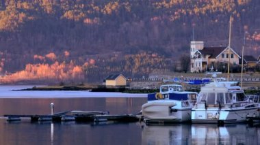 Sunset over leisure cruisers on a fjord beside a small norwegian town — Stock Video