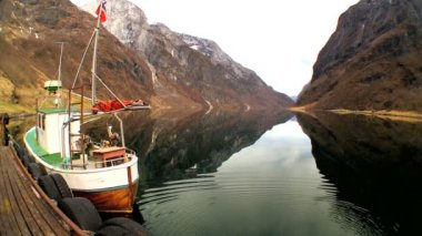 Fishing boat moored on mirror clear water of glacial fjord — Stock Video