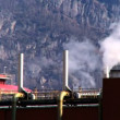 Oil refinery smoke polluting the air in a glacial valley - Stock Photo