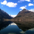 Stock Video: Time-lapse clouds over crystal waters of glacial fjord