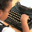 Cute african american schoolgirl using an old fashioned typewriter - Stock Photo