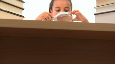 Cute african american schoolgirl using a spy glass with a book — Stock Video