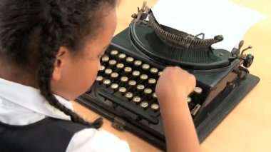 Cute african american schoolgirl using an old fashioned typewriter — Stock Video #20019357