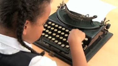 Cute african american schoolgirl using an old fashioned typewriter