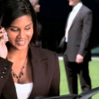 Young city business woman with colleagues talking on mobile(cell)phone - Stock Photo