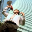 Ambitious city business man shouting his success through a megaphone - Stock Photo