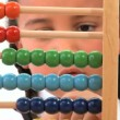 Cute african american schoolgirl early learning counting with an abacus - Stock Photo