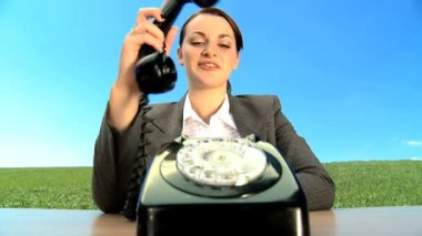 Concept shot of young businesswoman in city clothes using old-fashioned telephone — Stock Video