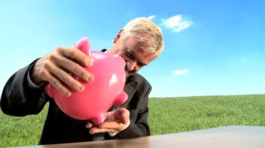 Businessman using money pig for green investment in an environmental future — Stock Video