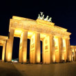 Visiting the Brandenburg Gate in Berlin when illuminated at night in time-lapse - Stock Photo