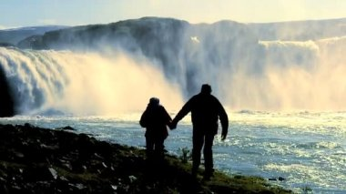 Couple in silhouette with stunning waterfall in background — Stock Video
