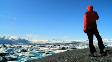 Lone female hiker watching glacial ice melting through global warming — Stock Video