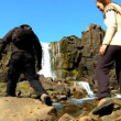Stock Video: Athletic young couple hiking alone across rough terrain to Pingvellir waterfall