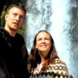 Stock Video: Young couple succeed in their hike to landmark waterfall