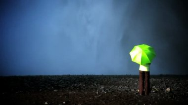 Concept shot of lone female standing on the edge of a waterfall with green umbrella — Stock Video