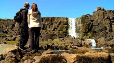 Athletic young couple hiking alone across rough terrain to Pingvellir waterfall, Iceland — Stock Video