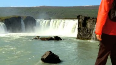 Female eco-tourist reaches the powerful waters of Godafoss waterfall, Iceland — Stock Video #20307211