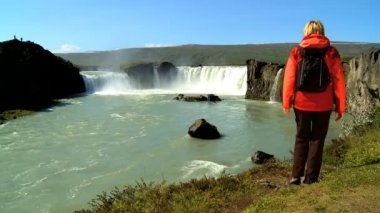 Female eco-tourist reaches the powerful waters of Godafoss waterfall, Iceland — Stock Video