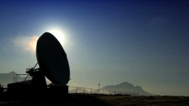Radio telescope (VLA) with geothermal steam pumping into the atmosphere behind — Stock Video