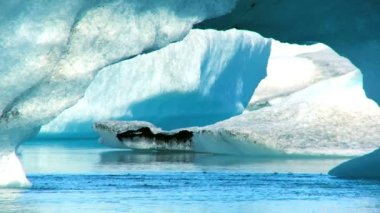 Glacial icebergs slowly melting into a lake through global warming