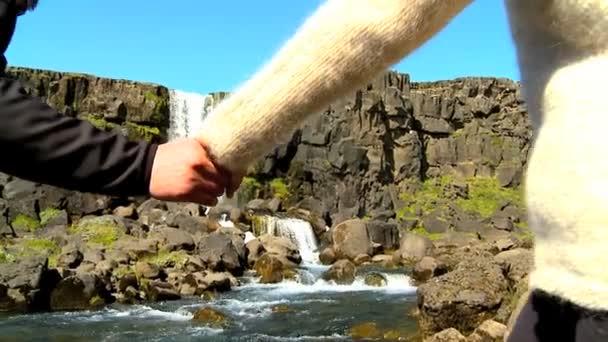 Athlétique jeune couple randonnée solitaire à travers un terrain accidenté à pingvellir cascade — Vidéo