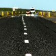 Traffic &amp; heat reflection on a tarmac countryside road - Stock Photo