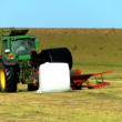 Farmer baling the harvested crop - Stock Photo