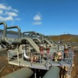 Steam for geothermal energy being piped from natural volcanic hot springs to power plant — Stok video