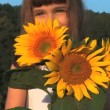 Stock Video: Cute little girl smelling sunflowers