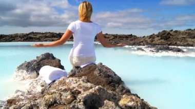 Lone female using relaxation therapy with geothermal hot springs in the foreground — Stock Video