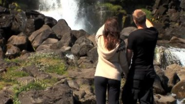Athletic young couple reach a landmark waterfall on their hiking adventure — Stock Video