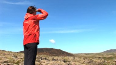 Lone female hiking across a barren Icelandic landscape — Stock Video