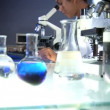 Medical professional working in lab with microscope and computer - 