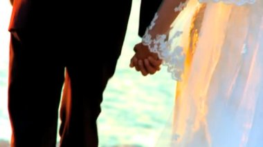 Young couple holding hands after their beach wedding-close-up