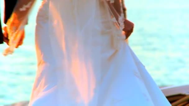 Pareja joven caminando junto a la playa después de su ceremonia de boda tropical — Vídeo de stock