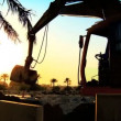 Mechanical excavator in silhouette,working on building site at sunset - Stock Photo
