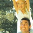 Stock Video: Young father holding his daughter on his shoulders while outdoors on summers day