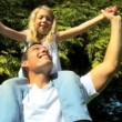 Stock Video: Young father laughing with his daughter on his shoulders while outdoors on summers day
