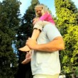 Stock Video: Young father holding his daughter while outdoors on summers day
