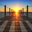 Stunning sunset over ocean & long wooden jetty - ストック写真