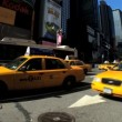 Fish-eye view of a fleet of yellow taxi cabs on Times Square, New York City - Stock Photo