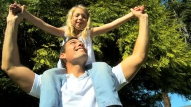 Young father laughing with his daughter on his shoulders while outdoors on a summers day — Stock Video