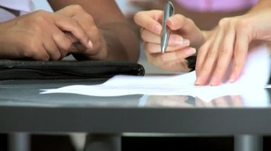 Hands only of multiethnic businesswomen signing papers in modern office in close-up — Stock Video